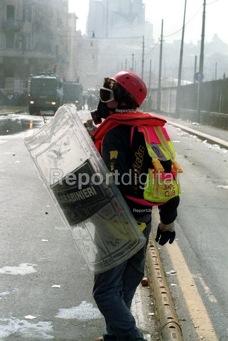 Anti Capitalist protesters with shield taken from riot police and tear gas mask, Genoa G8 summit. - Paul Mattsson - 2001-07-20