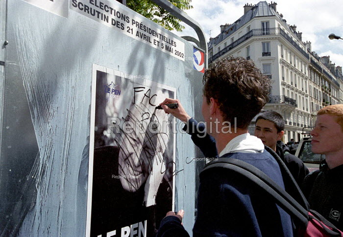 Protesters defacing a FN poster. Paris May Day anti nazi demonstration after the shock result for Jean-Marie Le Pen in the Presidential Election. - Paul Mattsson - 2002-04-30