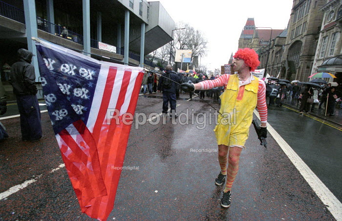 Stop the War on Iraq demonstration Manchester. Protester dressed in Ronald McDonald costume with mock American flag on the march - Paul Mattsson - 2003-03-08
