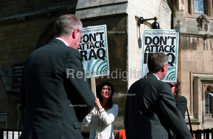 Stop the War Coalition lobby of parliament against war in Iraq. A couple of grey suited MPs walking into the House of Commons ignore anti war protesters outside - Paul Mattsson - 2003-03-18