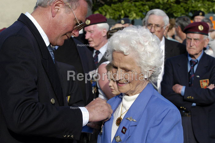 Female French resistance veteran receives a commemorative medal from a council official at local small town D Day sixtieth anniversary commemoration ceremony, Trouarn, Normandy, France - Paul Mattsson - 2004-06-06