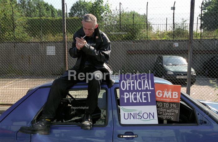 GMB & UNISON council workers strike against low pay. Picket sits on one Hackneys many abandoned cars outside Hackney social services offices on Morning Lane in east London - Paul Mattsson - 2002-07-17