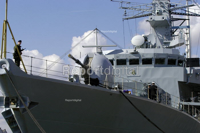 An armed guard on HMS Grafton, a British Royal Navy Duke Class Anti Submarine frigate which is moored at the side of Royal Victoria Dock. Defence Systems and Equipment International Exhibition, Excel, Docklands - Paul Mattsson - 2003-09-09