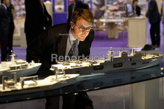 Man in a suit looking at model warships and aircraft carrier. Defence Systems and Equipment International Exhibition, Excel, Docklands - Paul Mattsson - 2003-09-09