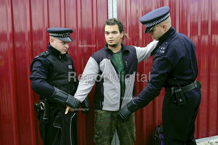 An anti arms trade protester is stopped and searched by Metropolitan Police officers under the draconian Terrorism Act 2000 while protesting outside the Defence Systems and Equipment International Exhibition at Excel, Docklands - Paul Mattsson - 2003-09-10
