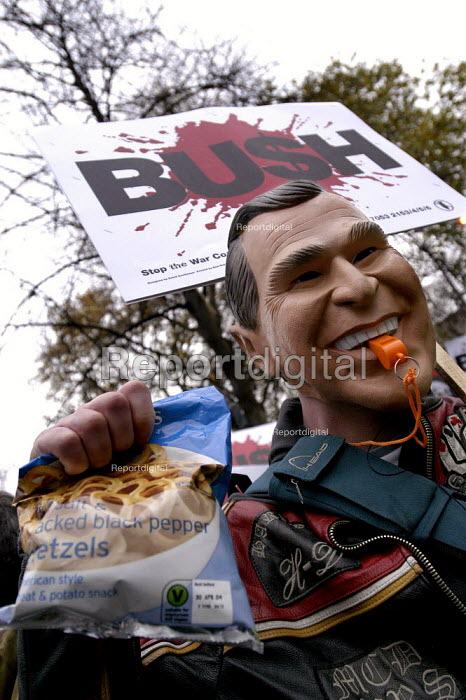 Stop The War Coalition demonstration against the visit of US President George W Bush to the UK. Protester wearing a George W Bush mask carries a bag of pretzels on the march through Central London - Paul Mattsson - 2003-11-20