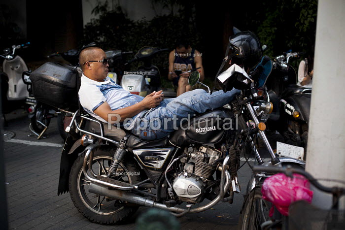 A man texting with his feet up on his motorcycle, Shanghai, China. - Connor Matheson - 2015-09-03