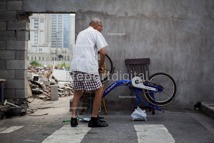 Elderly man pumping up his bicycle tire. Shanghai, China - Connor Matheson - 2015-09-03