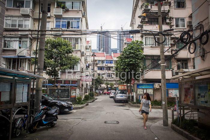 A woman walking through housing estate Pudong, Shanghai, China. - Connor Matheson - 2015-09-05