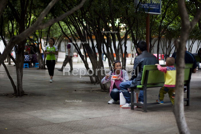 A family sitting on a bench. Cuihu Park, Kunming, Yunnan Province, China. - Connor Matheson - 2015-09-10
