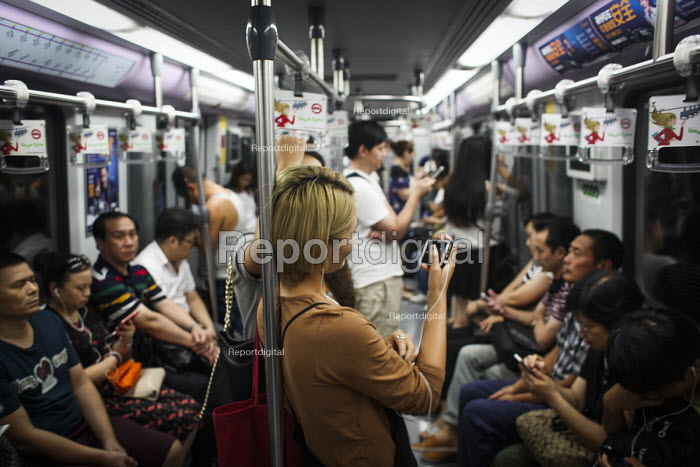A woman watching a TV program on her phone while commuting on the subway system. Shanghai, China. - Connor Matheson - 2015-09-07