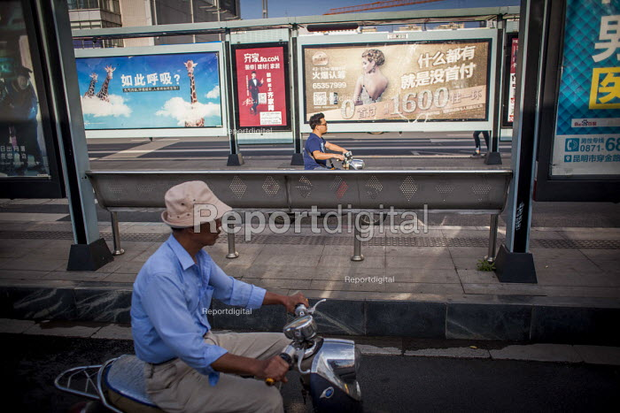 Locals riding scooters past advertisement hoardings. Kunming, Yunnan Province, China. - Connor Matheson - 2015-09-10