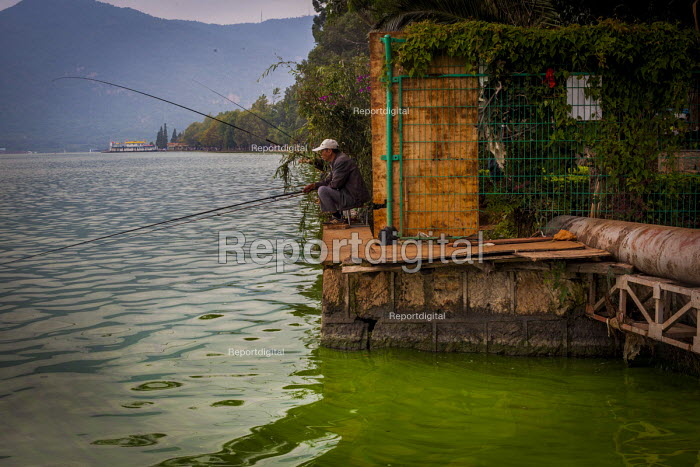 Fishing in Dianchi Lake which has gone green with pollution, it is estimated that around 55% of the fish are dead. Kunming, Yunnan Province, China. Untill 1990 city waste water was pumped untreated into the lake and agricultural runoff has further polluted the water - Connor Matheson - 2015-09-13