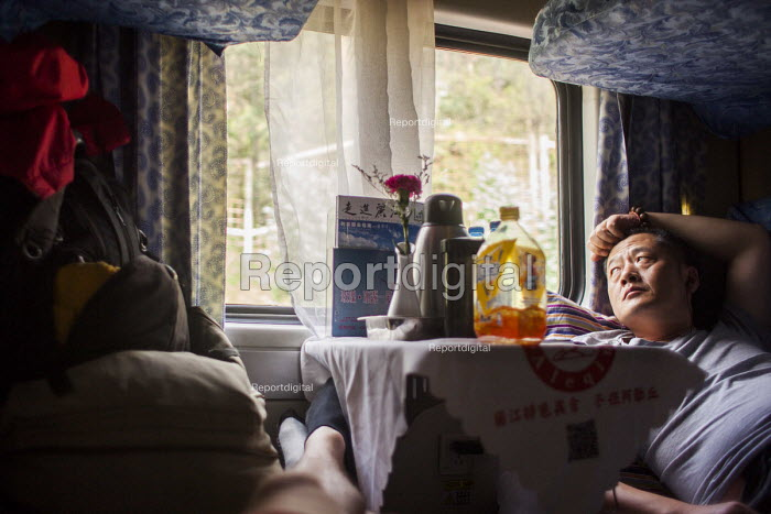 A Chinese man looking out the window on a train ride. Yunnan Province, China. - Connor Matheson - 2015-09-16