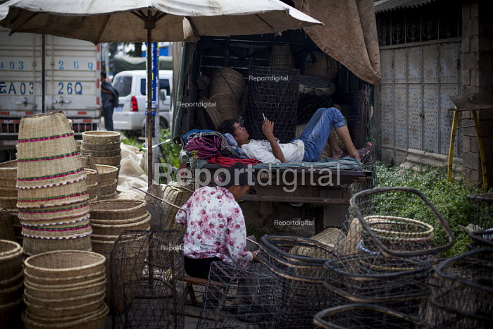 Man resting and woman weaving baskets, busy market, Dali, Yunnan Province, China - Connor Matheson - 2015-09-18