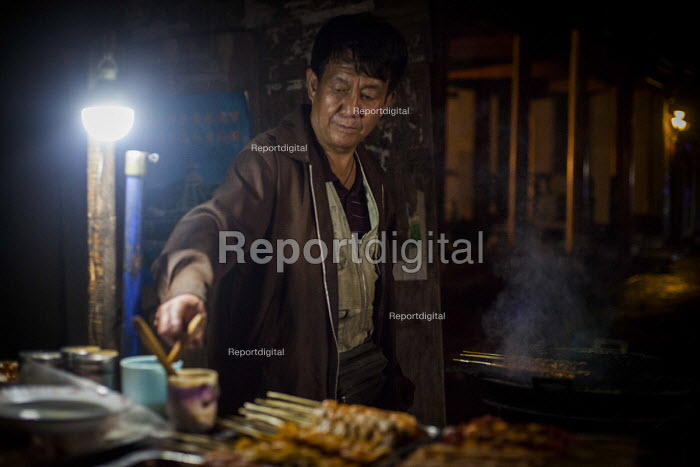 A worker cooking street food. Dali, China. - Connor Matheson - 2015-09-19