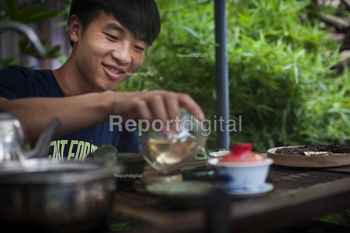 A young man pouring Chinese tea. Lijiang, Yunnan Province, China. - Connor Matheson - 2015-09-21
