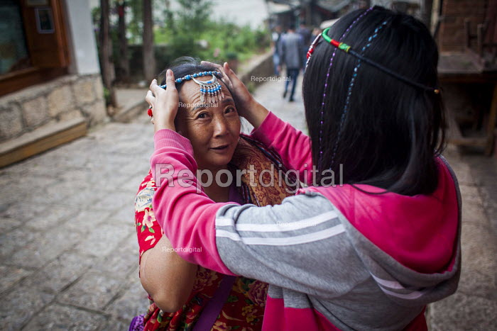 Young people selling handmade jewellery to wealthy Chinese tourists. Lijiang, Yunnan Province, China. - Connor Matheson - 2015-09-22