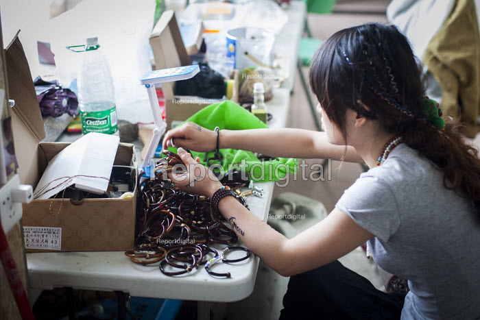 Young people making handmade jewellery in a Chinese youth hostel to sell to wealthy Chinese Tourists. Lijiang, Yunnan Province, China. - Connor Matheson - 2015-09-22