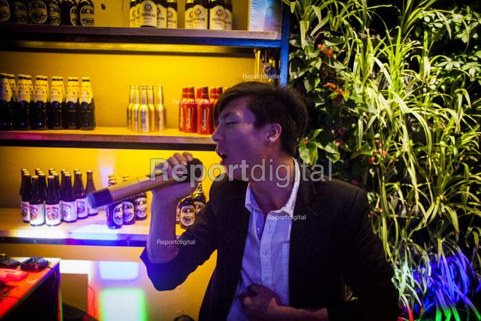 A bar manager karaoke singing after his shift. Kunming, Yunnan Province, China. - Connor Matheson - 2015-09-26