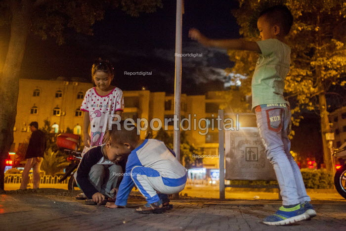 Children playing on the street late at night. Dongcheng, Yunnan Province, China. - Connor Matheson - 2015-09-28