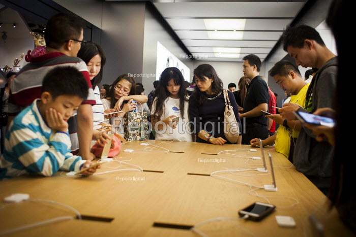 Wealthy Chinese tourists looking at the Iphone. Apple Store, Nanjing Road, Shanghai, China. - Connor Matheson - 2015-10-04