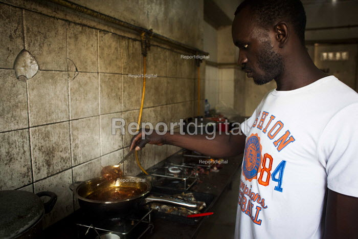 Refugee from Africa cooking food in the communal kitchen. Marsa Open Centre, Malta. - Connor Matheson - 2015-07-14