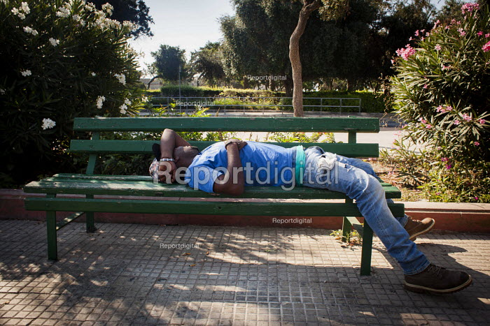 A man rests after working during the morning, bus stop for the Hal Far Refugee Camp. Valletta, Malta. - Connor Matheson - 2015-07-19