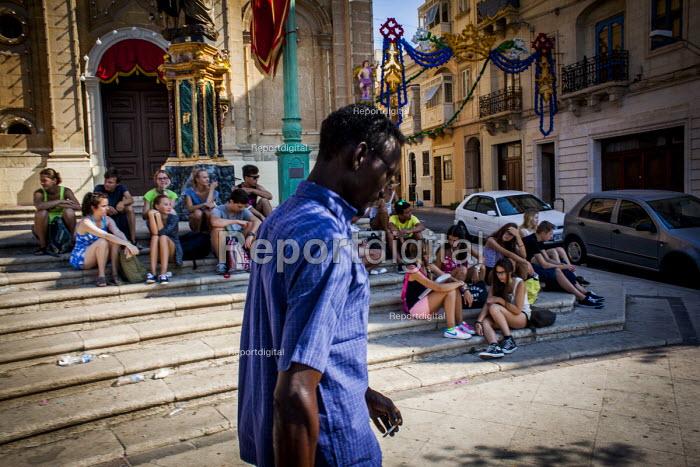 Malta, Mahjoub a Sudanese refugee walking past tourists visiting Malta. Msida, Malta. - Connor Matheson - 2015-07-20