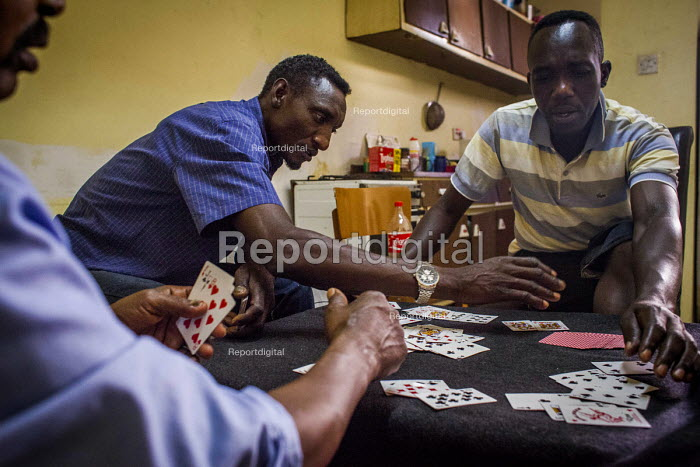 Malta, Mahjoub, a Sudanese refugee playing cards with his friends who are also refugees from Sudan. Valletta, Malta. - Connor Matheson - 2015-07-20