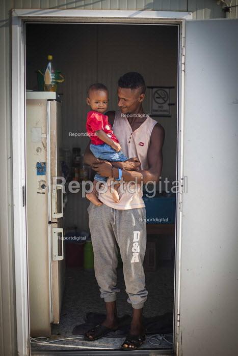Somali refugee and his child, Hal Far Refugee Camp, Malta. - Connor Matheson - 2015-08-10