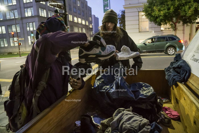 Berkeley, California, Two homeless youth picking out trainers from the free box, Berkeley Post Office - David Bacon - 2015-11-03