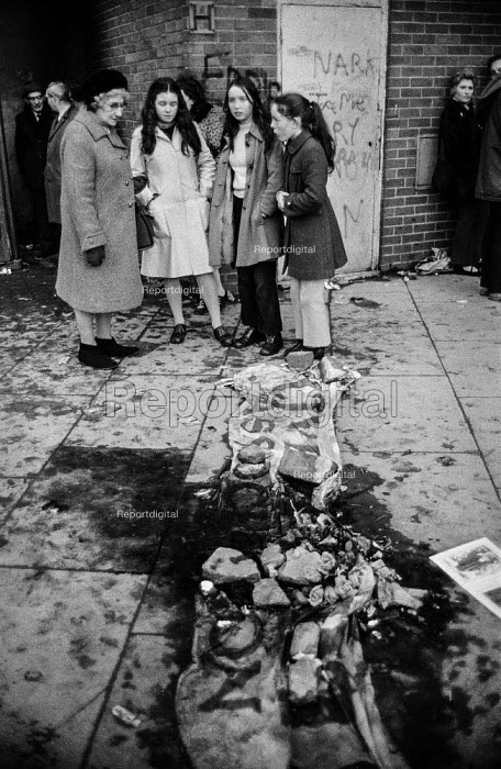 Bloody Sunday, Derry 1972. Flowers and Civil Rights Association banner laid in a pool of blood where one of the Derry 13 was shot dead by paratroopers during a civil rights march. - Martin Mayer - 1972-01-31
