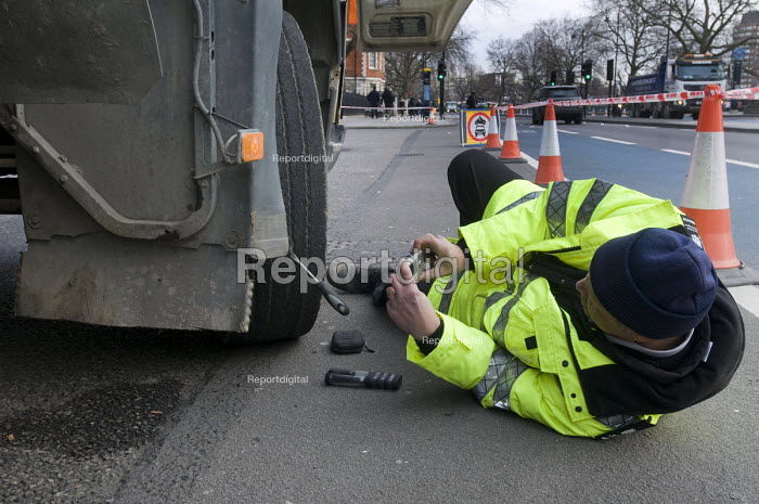 Trucks pulled over as part of the regular roadside checks by DVSA staff to ensure that HGVs are safe to drive on British roads. A vehicle inspector with many years experience inspects worn tyres on an HGV and photographs the evidence. - Stefano Cagnoni - 2015-03-06