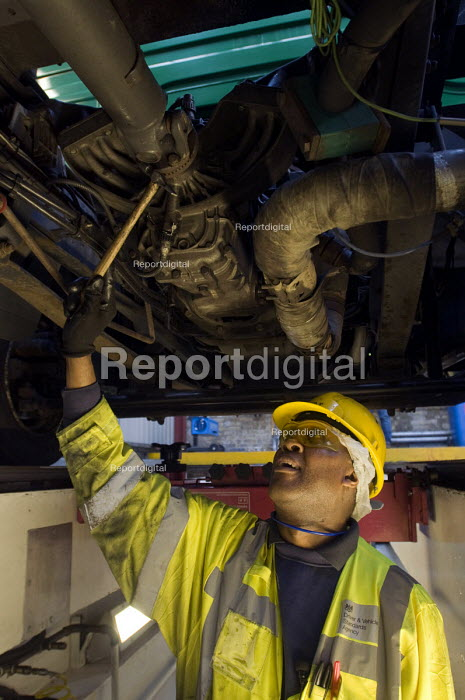 A vehicle inspector with many years experience inspects a bus engine from a garage inspection pit - Stefano Cagnoni - 2015-03-06