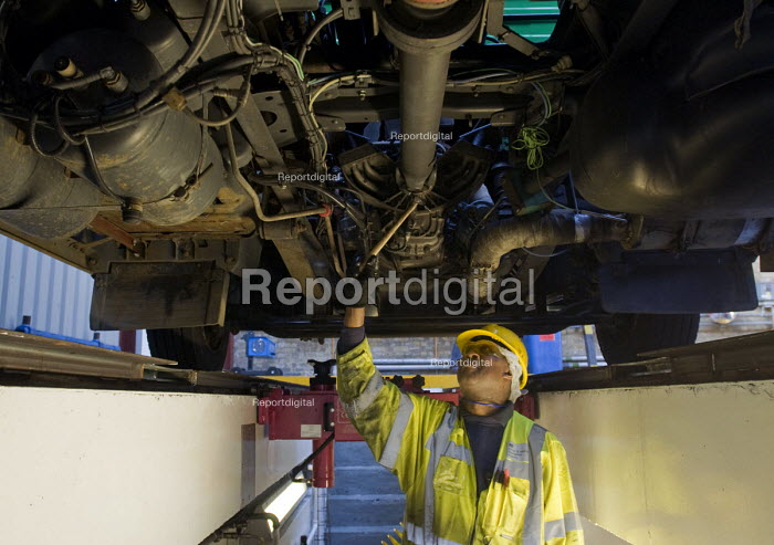 A vehicle inspector with many years experience inspects a bus engine from a garage inspection pit. - Stefano Cagnoni - 2015-03-06