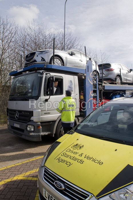 Trucks pulled over as part of the regular roadside checks by DVSA staff to ensure that HGVs are safe to drive on British roads. A vehicle inspector at a permanent check site off the M25 prepares to inspect a car transporter - Stefano Cagnoni - 2015-03-10