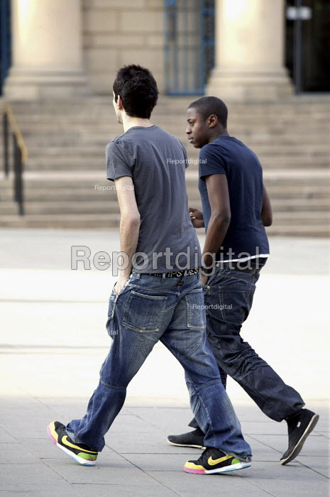 Male students stride in step across the city centre of Sheffield back to Sheffield University. - David Mansell - 2009-03-20