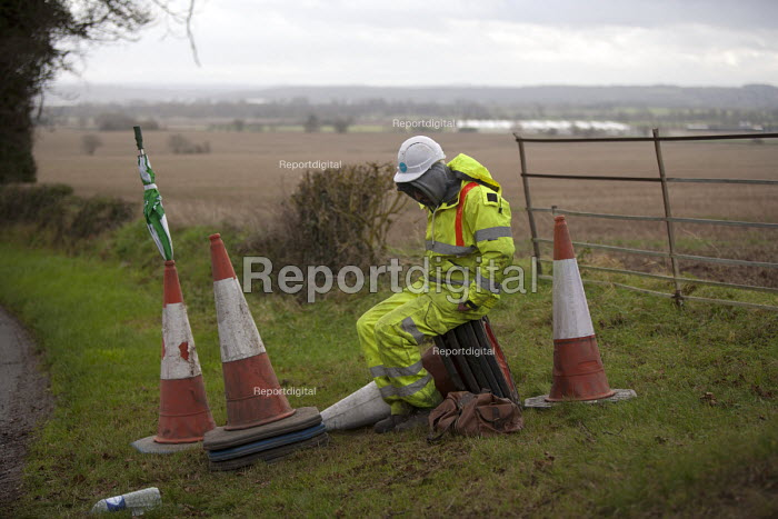 Bored and cold worker controlling traffic, keeping a rural road closed but allowing lorries through for resurfacing, Warwickshire - John Harris - 2015-12-10
