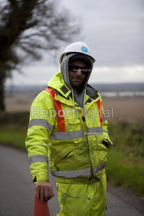 Worker controlling traffic, keeping a rural road closed but allowing lorries through for resurfacing, Warwickshire - John Harris - 2015-12-10