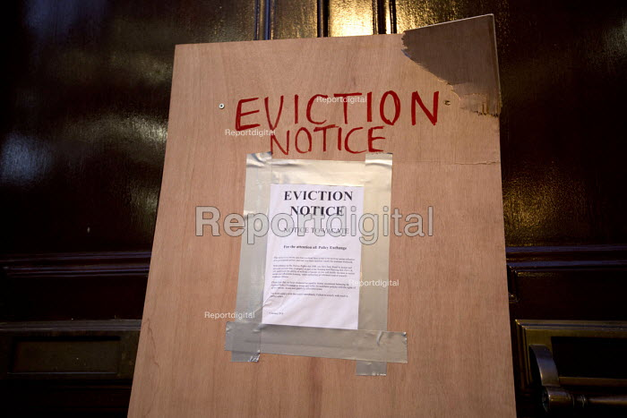 Activists board up the doors of the Policy Exchange with an Eviction Notice in Housing Bill protest. Westminster, London - Jess Hurd - 2016-01-05