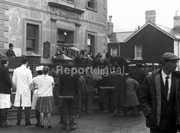 Aberfan disaster, a coffin is lifted into a tempory mortuary. 116 children and 28 adults were killed when a slag heap collapsed onto the pit village, South Wales - NLA - 1966-10-15