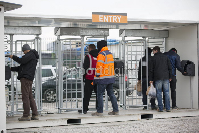 Refugees in the official container camp are biometrically fingerprint tested on entry to the camp, Calais, France. - Jess Hurd - 2016-02-26