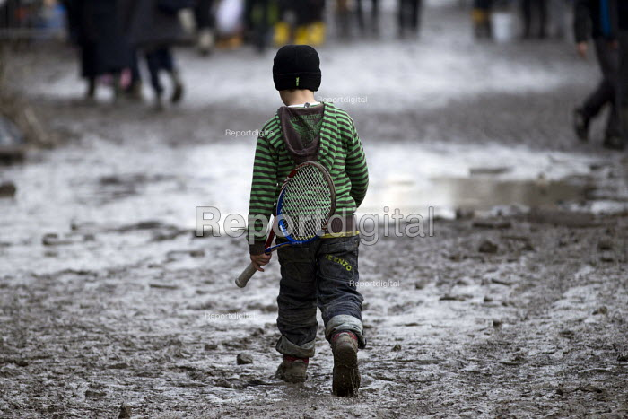 Refugee child with a tennis racket in the makeshift camp. Grande-Synthe, France. - Jess Hurd - 2016-02-25