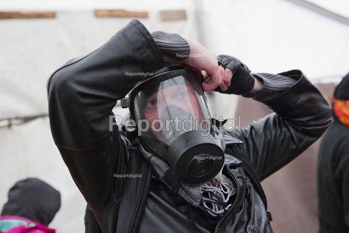 Jason N. Parkinson, video journalist putting on a gas mask. Demolition of the Jungle refugee camp, Calais, France - Jess Hurd - 2016-03-03