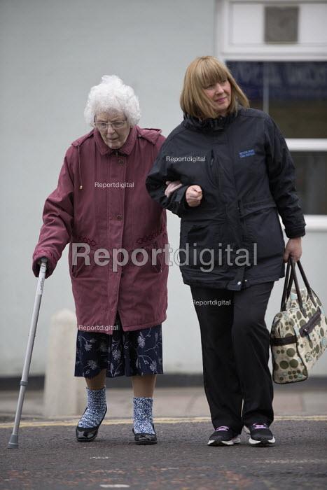 Carer helping an elderly woman cross the road, Easington Lane, Hetton, Tyne and Wear - John Harris - 2016-03-24