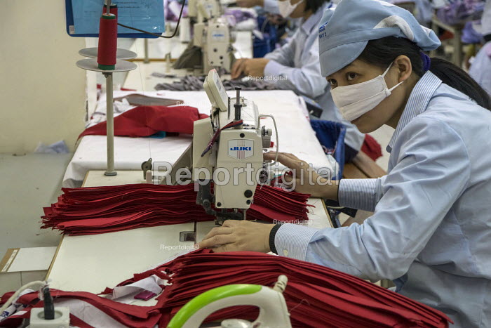 Hanoi Vietnam Sewing machine operators at work, May 10 Garment Factory. The factory was state owned when it began 29 years ago and is now half-owned by private capital. It makes garments for LExpress, FOB and other mostly American companies. About 2500 workers work in the Hanoi factory. - David Bacon - 2015-12-15