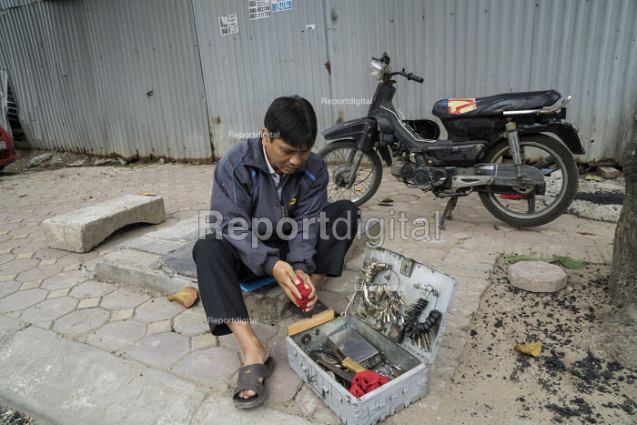 Hanoi, Vietnam, A man has a small business on the sidewalk duplicating keys for scooters. - David Bacon - 2015-12-09