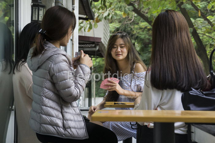 Hanoi, Vietnam, Young women play cards at a cafe - David Bacon - 2015-12-09