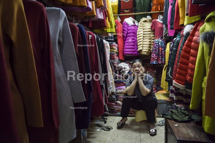 Exhausted shopworker, stall selling cloth, Dong Xuan Market, Hanoi, Vietnam - David Bacon - 2015-12-09